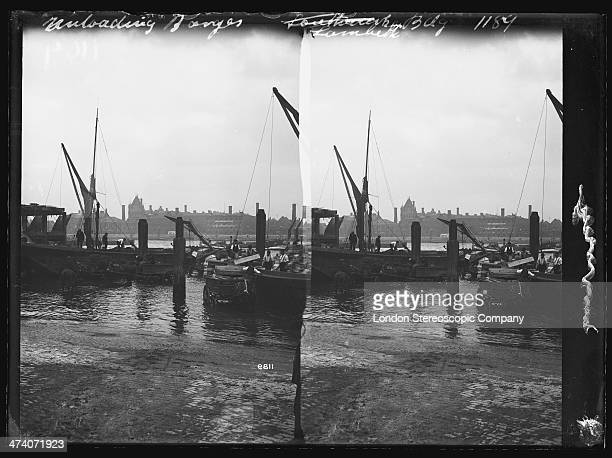 A stereoscopic image of bargees unloading cargo onto horsederawn carts on the south bank of the Thames at Lambeth London circa 1885