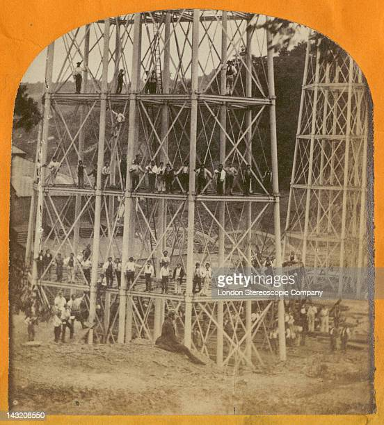A stereoscopic image of construction workers crowding the piers of the Crumlin Viaduct during its construction over the village of Crumlin in South...