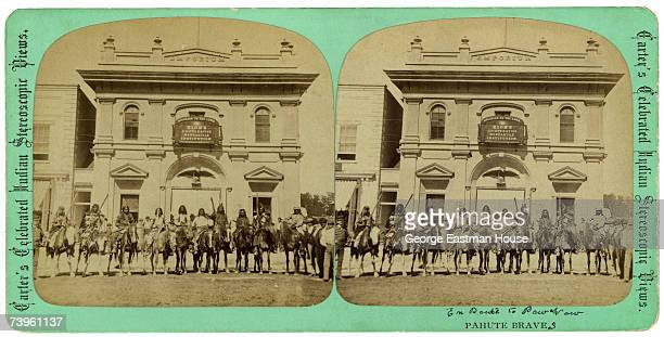 Stereoscopic portrait of a group of ten Native Americans of the Paiute tribe as they pose on horseback outside of the Zion CoOperative Mercantile...