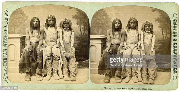 Stereoscopic portrait of three unidentified girls of the Paiute people as they sit together shirtless but covered in body paint in front of a...