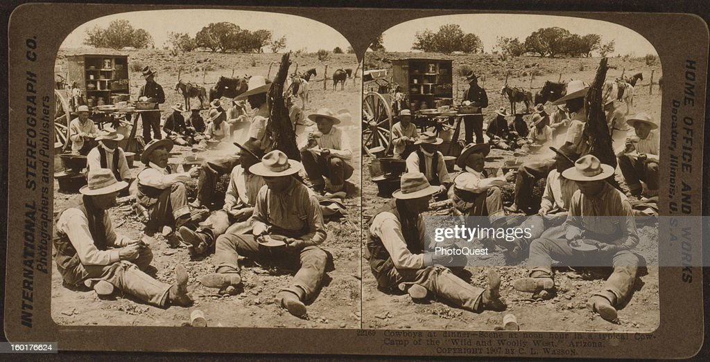 Stereoscopic view of a group of cowboys as they sit on the ground and eat a lunch time meal from the 'chuck wagon,' Arizona, 1907.