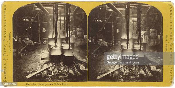 Stereoscopic view of several women and children as they pose with a number of steaming metal pots suspended over a fire on stripped tree branches,...