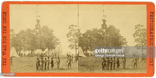 Stereoscopic view shows a group of Union soldiersa as they watch American inventor and balloonist Professor Thaddeus S C Lowe ascend in 'Intrepid' a...