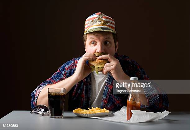 Stereotypical American man eating a burger