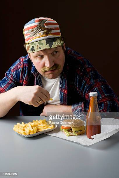 Stereotypical American man eating a fast food meal