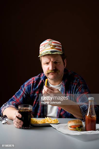 Stereotypical American man holding a french fry and staring at it
