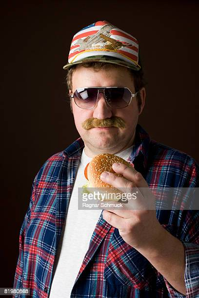 stereotypical american man holding a hamburger - fake man stock photos and pictures
