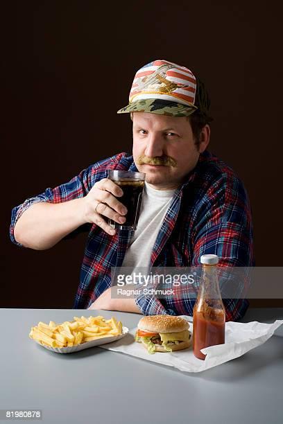 stereotypical american man with burger, fries and a cola - unterschicht stereotypen stock-fotos und bilder