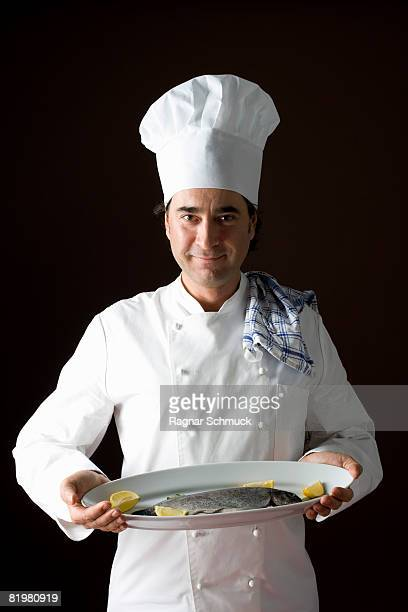 Stereotypical chef posing with a platter of fish