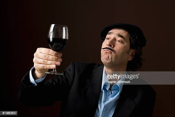 A stereotypical French man staring at a glass of red wine