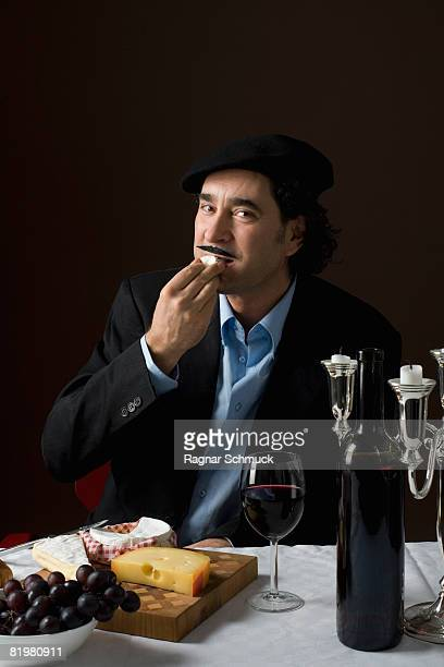 Stereotypical French man tasting French cheese
