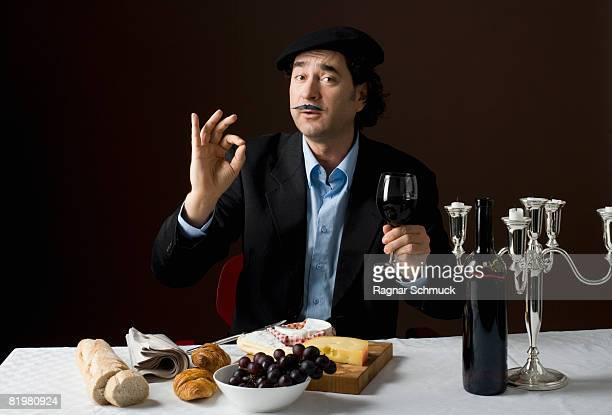 stereotypical french man with stereotypical french food - french culture stock pictures, royalty-free photos & images