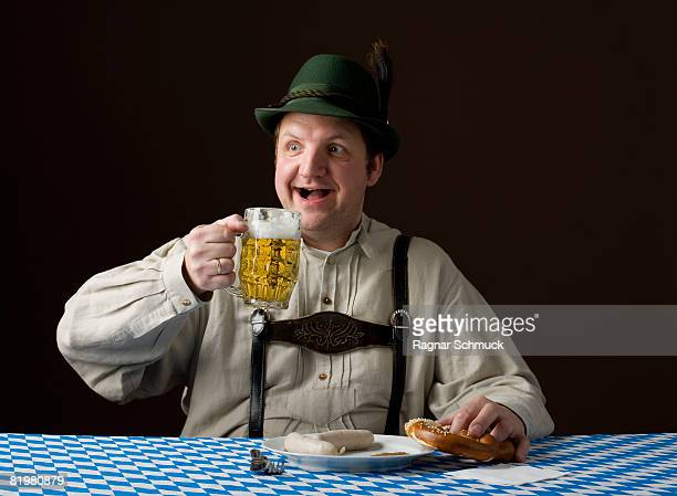 stereotypical german man holding a beer and a pretzel - german culture stock pictures, royalty-free photos & images