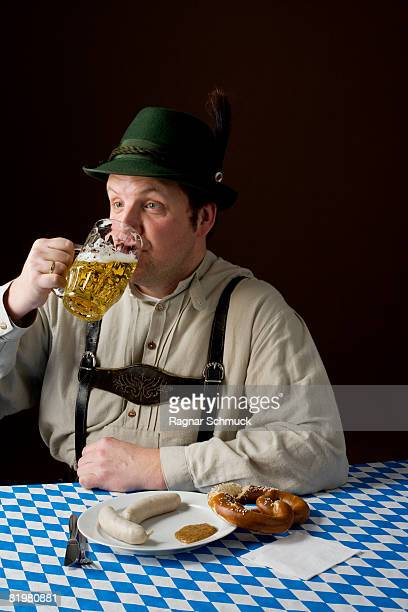 Stereotypical German man in Bavarian costume drinking a beer and German meal
