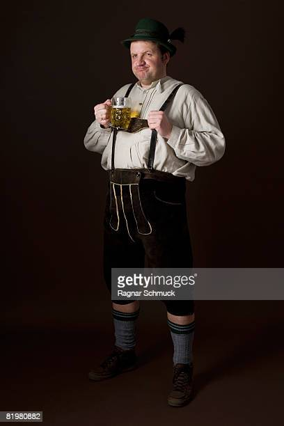 Stereotypical German man in Bavarian costume holding a beer