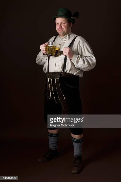 stereotypical german man in bavarian costume holding a beer - vestido tradicional fotografías e imágenes de stock
