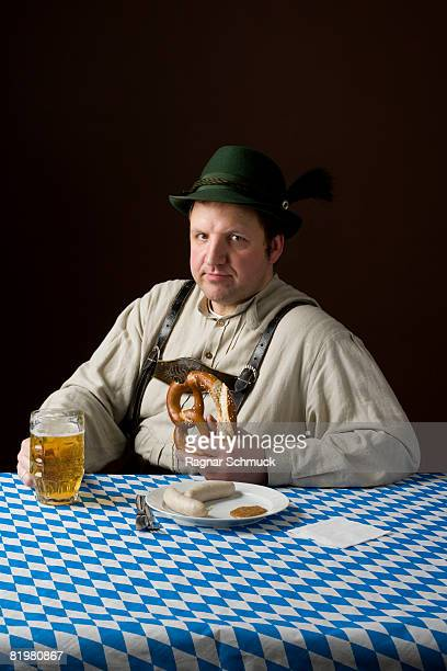 Stereotypical German man in Bavarian costume wiping mouth at a table with a beer and German meal
