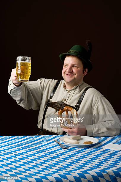 Stereotypical German Man toasting a glass of beer and holding a pretzel