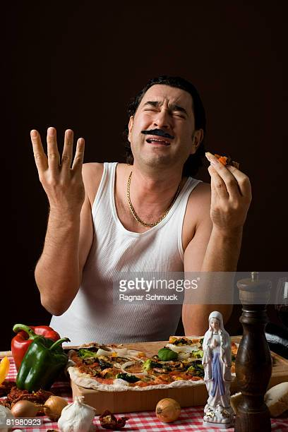 Stereotypical Italian Man eating pizza and gesturing with his hand