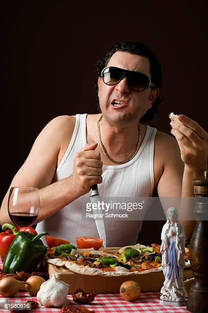 Stereotypical Italian Man sticking a knife in a cutting board aggressively and eating pizza