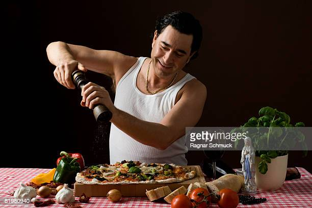 stereotypical italian man using a pepper mill on his pizza - pepper mill stock pictures, royalty-free photos & images