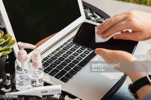 sterilize cellphone surface using disposable wipes outdoor - 消毒用アルコール ストックフォトと画像