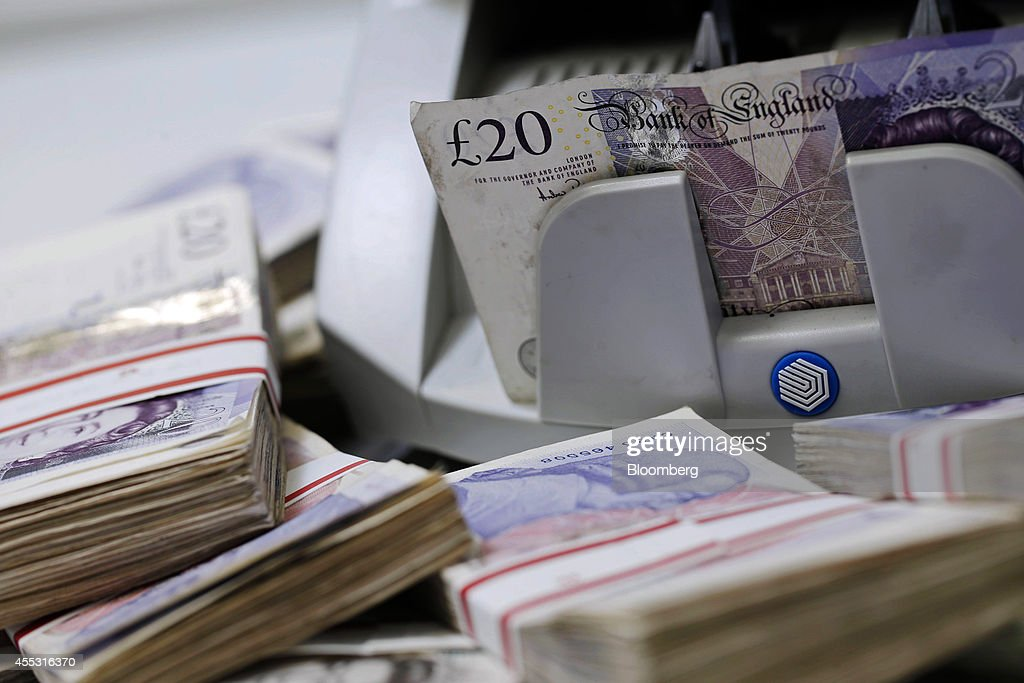 Sterling 20 pound banknotes pass through an automated currency counting machine in this arranged photograph inside a Travelex store, operated by Travelex Holdings Ltd., in London, U.K., on Friday, Sept. 12, 2014. The pound, already suffering its worst month in more than a year, has the potential to tumble 10 percent should the Scots vote for independence from the U.K., according to economists surveyed by Bloomberg. Photographer: Matthew Lloyd/Bloomberg via Getty Images