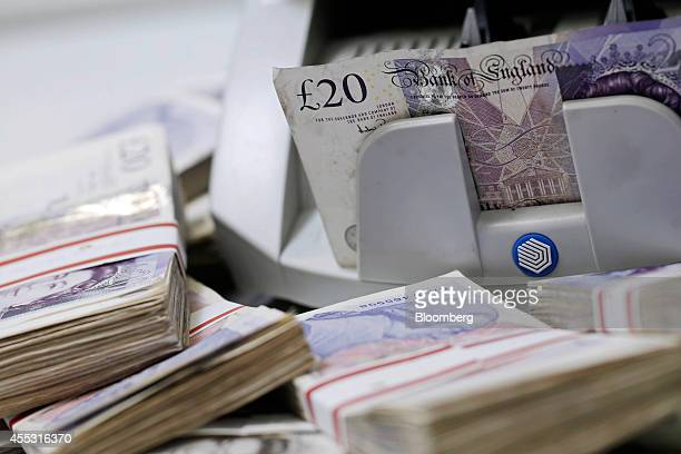 Sterling 20 pound banknotes pass through an automated currency counting machine in this arranged photograph inside a Travelex store operated by...