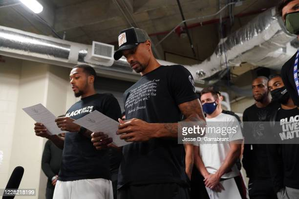 Sterling Brown and George Hill of the Milwaukee Bucks reads a statement to the media on August 26, 2020 at AdventHealth Arena at ESPN Wide World of...