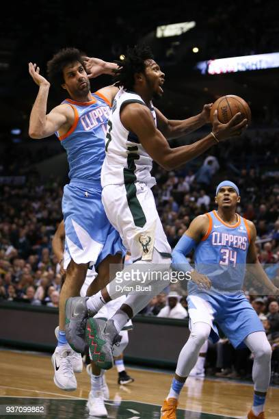 Sterling Brown of the Milwaukee Bucks attempts a shot past Milos Teodosic of the Los Angeles Clippers in the second quarter at the Bradley Center on...