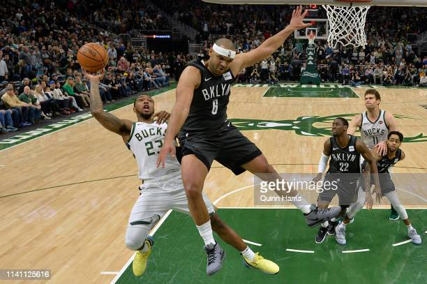Sterling Brown of the Milwaukee Bucks shoots against Jared Dudley of the Brooklyn Nets in the second half at Fiserv Forum on April 06 2019 in...