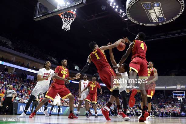 Sterling Brown of the Southern Methodist Mustangs competes for a loose ball against Chimezie Metu and Charles Buggs of the USC Trojans in the first...