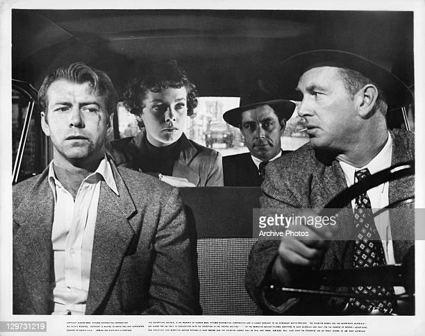 Sterling Hayden driving Gene Nelson with Phyllis Kirk and Richard Benjamin in the back in a scene from the film 'Crime Wave' 1954
