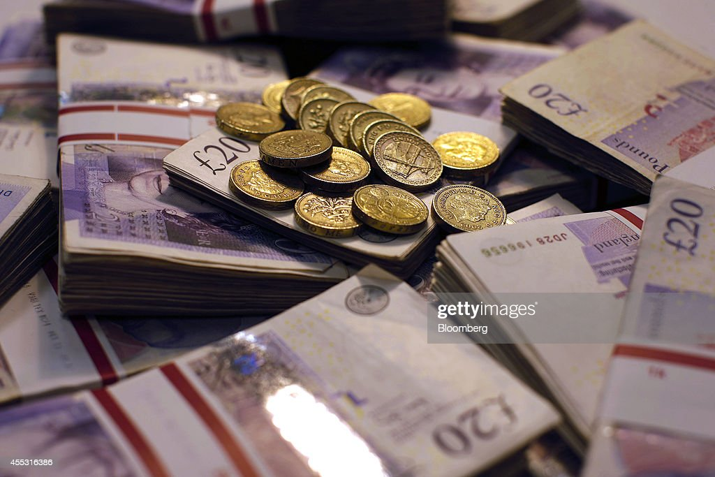 Sterling one pound coins and bundles of 20 pound sterling banknotes are arranged for a photograph inside a Travelex store, operated by Travelex Holdings Ltd., in London, U.K., on Friday, Sept. 12, 2014. The pound, already suffering its worst month in more than a year, has the potential to tumble 10 percent should the Scots vote for independence from the U.K., according to economists surveyed by Bloomberg. Photographer: Matthew Lloyd/Bloomberg via Getty Images