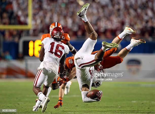 Sterling Shepard of the Oklahoma Sooners is upended by T.J. Green of the Clemson Tigers in the fourth quarter during the 2015 Capital One Orange Bowl...