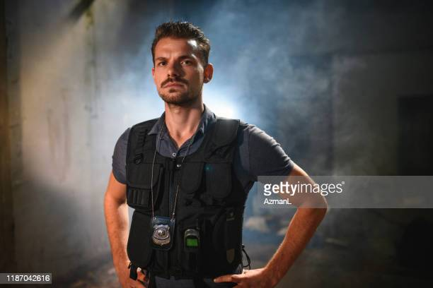 stern caucasian male police officer at nighttime crime scene - privateinvestigator stock pictures, royalty-free photos & images