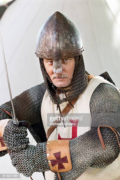 stern looking knight in a fighting pose - historical reenactment stock photos and pictures
