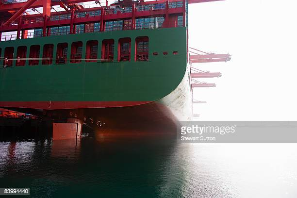 Stern of a green and red docked cargo ship.