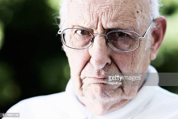 stern old man glares over his spectacles: grumpy old man - grumpy old man stock pictures, royalty-free photos & images