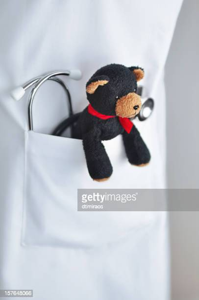 stethoscope and child's teddy bear in doctor's lab coat pocket - paediatrician stock pictures, royalty-free photos & images