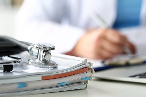 Stethoscope head lying on medical forms closeup 852404126