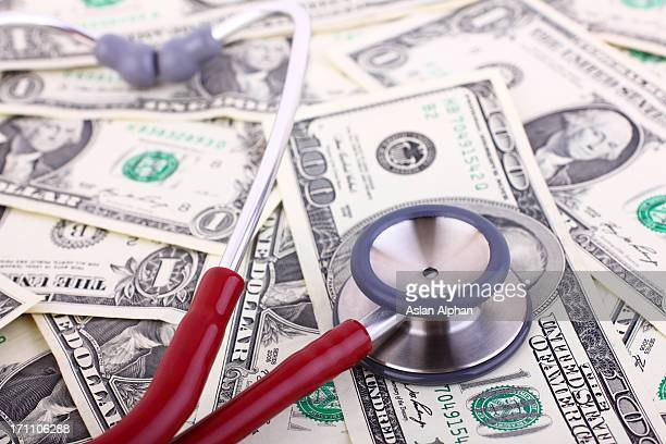 stethoscope on various monetary denominations - expense stock pictures, royalty-free photos & images