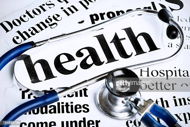 Stethoscope rests on newspaper headlines about health issues