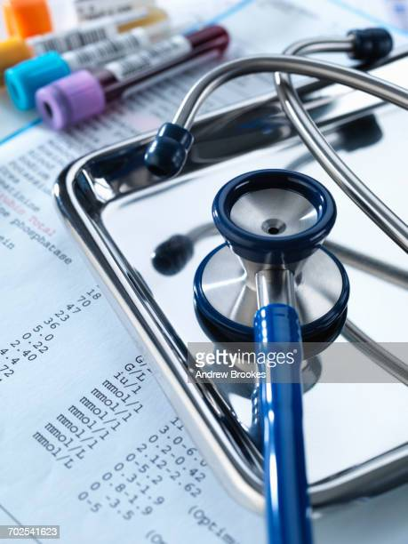 Stethoscope sitting on a tray with test results and patient specimens