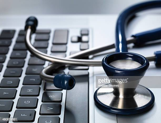 stethoscope sitting on laptop illustrating online healthcare and doctor's desk - hypochondria stock photos and pictures
