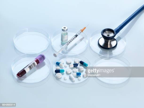 Stethoscope, vaccine, blood sample and variety of medicine in petri dish