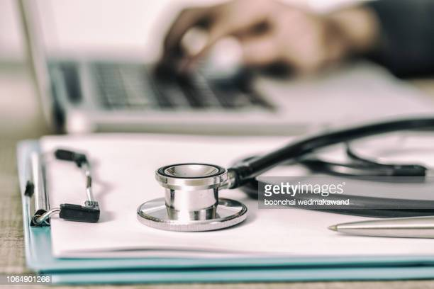 Stethoscope with clipboard and Laptop on desk,Doctor working.