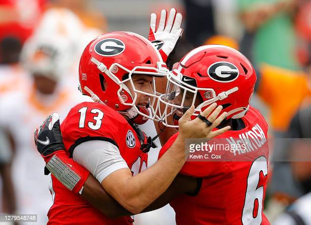 Stetson Bennett of the Georgia Bulldogs reacts after rushing for a touchdown against the Tennessee Volunteers with Kenny McIntosh during the first...