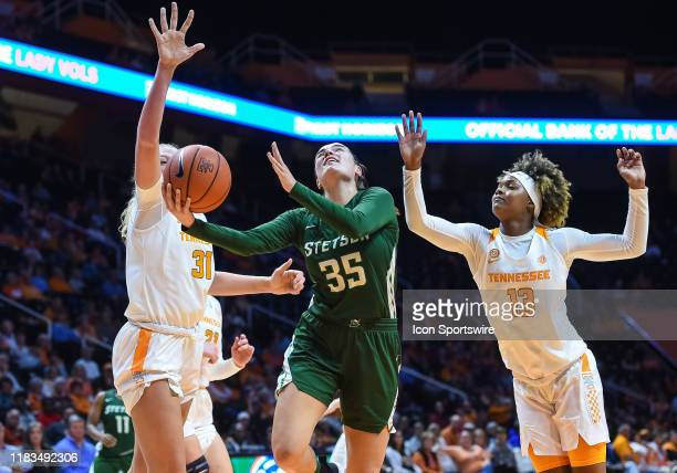 Stetson Hatters forward Kendall Lentz drives between Tennessee Lady Vols center Emily Saunders and guard Jazmine Massengill during a college...