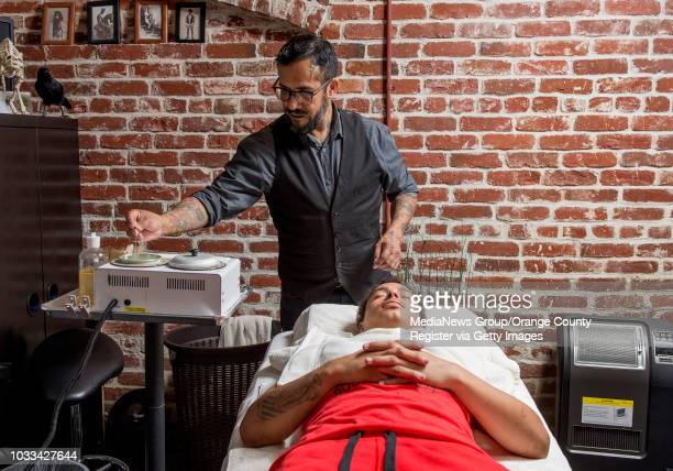 Stev owner of Villain Manscape in Placentia left dips an applicator into hot wax as he prepares to shape Michael's eyebrows INFORMATION...